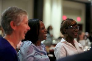 Donna Williams (c) and her daughter Da-Jae Miller (r), clients of Servant of Justice Honoree Tom Papson, listen to his speech alongside Tom's wife, Toby Singer (l)