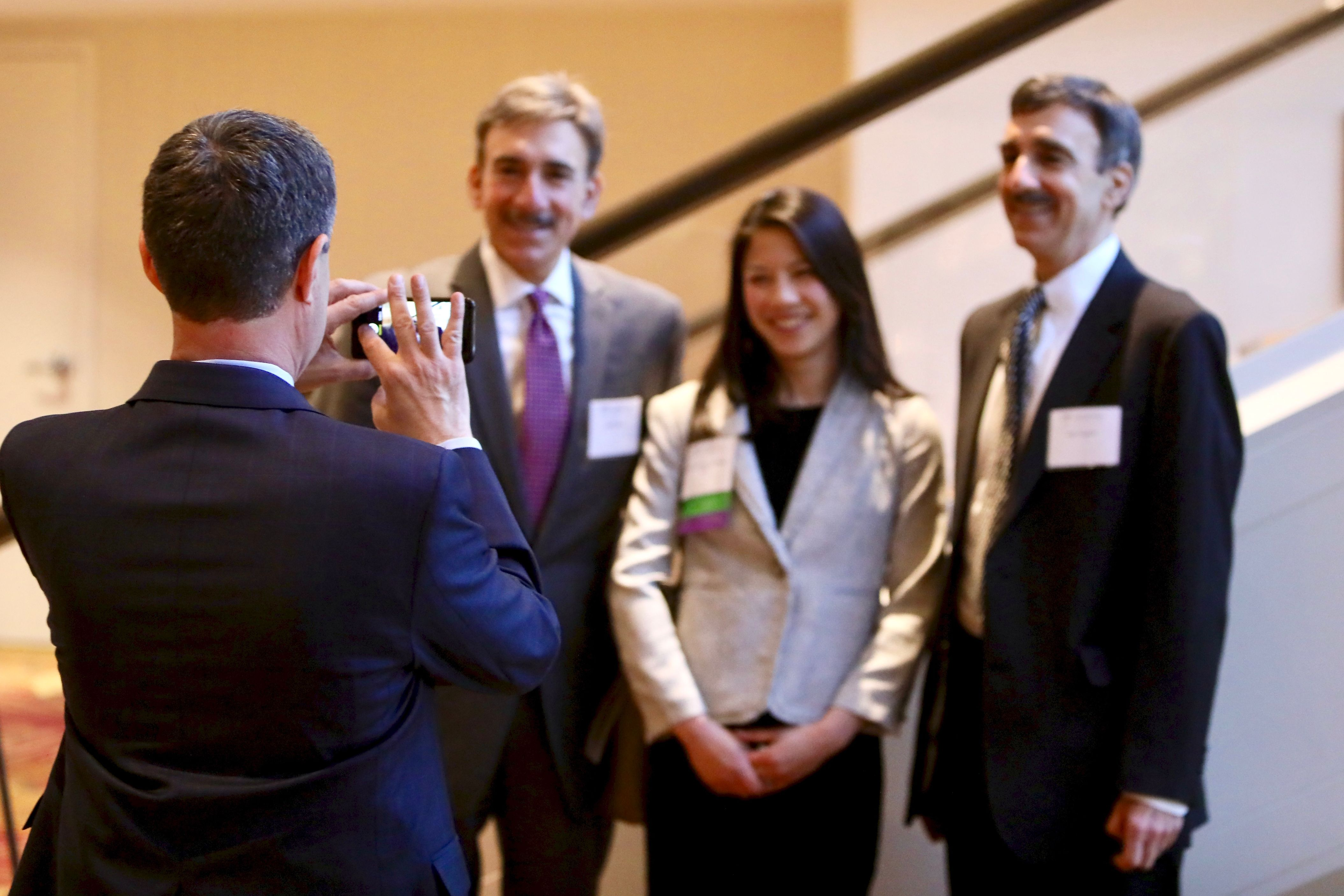 Executive Director Eric Angel snaps a photo of Supervising Attorney Jennifer Lavallee with Don and Ron Papson, honoree Tom Papson's twin brothers